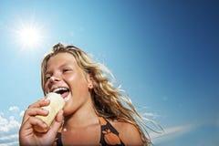 Muchacha que come el helado al aire libre Foto de archivo libre de regalías