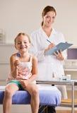 Muchacha que come el lollipop en oficina del doctor Foto de archivo