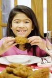 Muchacha que come el palillo de pollo frito Foto de archivo