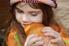 Muchacha que come el pan Imagenes de archivo