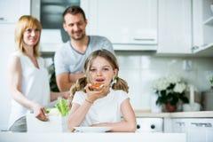 Muchacha que come el pan con el tomate y la cebolleta en cocina fotografía de archivo