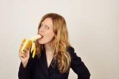 Muchacha que come el plátano en traje negro de la oficina Fotografía de archivo