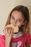 Muchacha que come el queso imagen de archivo