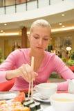 Muchacha que come el sushi Imagen de archivo libre de regalías