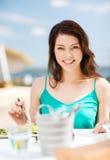 Muchacha que come en café en la playa Imagen de archivo