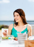 Muchacha que come en café en la playa Imagenes de archivo