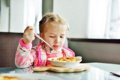 Muchacha que come en restaurante Imagen de archivo libre de regalías
