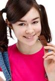 Muchacha que come la barra del chocolate aislada en blanco Foto de archivo