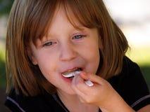 Muchacha que come la cucharada Imágenes de archivo libres de regalías