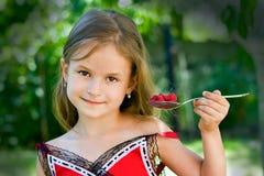 Muchacha que come la frambuesa Imágenes de archivo libres de regalías