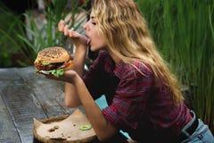 Muchacha que come la hamburguesa Imagen de archivo libre de regalías
