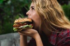 Muchacha que come la hamburguesa Imágenes de archivo libres de regalías