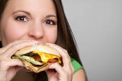 Muchacha que come la hamburguesa Imagenes de archivo