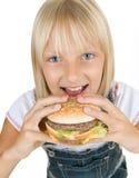 Muchacha que come la hamburguesa. Alimentos de preparación rápida Foto de archivo libre de regalías