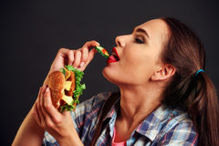 Muchacha que come la hamburguesa con apetito Foto de archivo