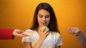 Muchacha que come la manzana en vez del buñuelo, del bocado sano y de las vitaminas contra la comida azucarada almacen de metraje de vídeo