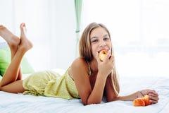 Muchacha que come la manzana y que se relaja en dormitorio Imagenes de archivo