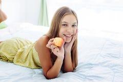 Muchacha que come la manzana y que se relaja en dormitorio Imagen de archivo libre de regalías