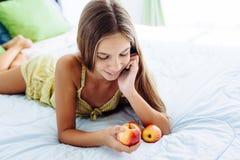 Muchacha que come la manzana y que se relaja en dormitorio Fotos de archivo libres de regalías