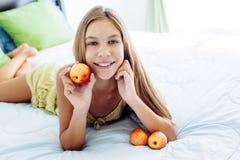Muchacha que come la manzana y que se relaja en dormitorio Imagen de archivo