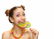 Muchacha que come la piruleta colorida Imagenes de archivo