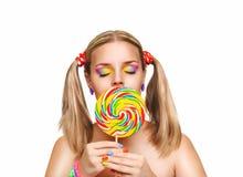 Muchacha que come la piruleta colorida Fotos de archivo