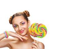 Muchacha que come la piruleta colorida Foto de archivo libre de regalías