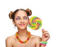 Muchacha que come la piruleta colorida Foto de archivo