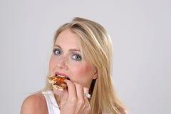 Muchacha que come la pizza Imagenes de archivo