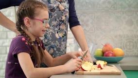 Muchacha que come la rebanada de la manzana en cocina Niño que come la fruta con la madre en cocina almacen de video