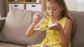 Muchacha que come la torta en casa almacen de metraje de vídeo