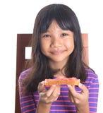 Muchacha que come la tostada I del pan Foto de archivo libre de regalías