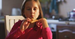 Muchacha que come la tostadora en la tabla almacen de metraje de vídeo