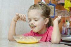 Muchacha que come las gachas de avena en la cocina Imagen de archivo
