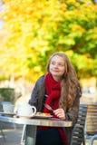 Muchacha que come las galletas en un café parisiense Fotos de archivo libres de regalías