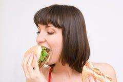 Muchacha que come las hamburguesas imagen de archivo libre de regalías