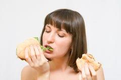 Muchacha que come las hamburguesas Fotos de archivo