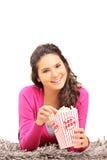 Muchacha que come las palomitas y que miente en una alfombra Imagen de archivo libre de regalías