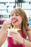Muchacha que come las patatas fritas Imagenes de archivo