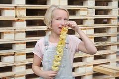 Muchacha que come las patatas fritas en un palillo Junk Food, comida de la calle, bocado en un paseo Imagen de archivo