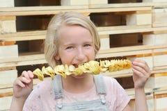 Muchacha que come las patatas fritas en un palillo Junk Food, comida de la calle, bocado en un paseo Fotografía de archivo