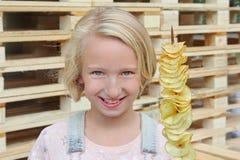 Muchacha que come las patatas fritas en un palillo Junk Food, comida de la calle, bocado en un paseo Foto de archivo