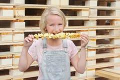 Muchacha que come las patatas fritas en un palillo Junk Food, comida de la calle, bocado en un paseo Imagenes de archivo