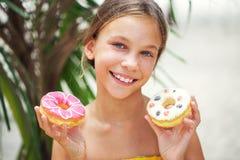 Muchacha que come los anillos de espuma Fotos de archivo