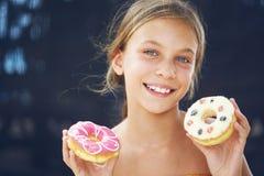 Muchacha que come los anillos de espuma Fotos de archivo libres de regalías
