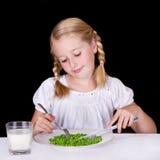 Muchacha que come los guisantes Fotografía de archivo
