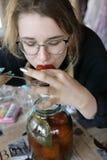 Muchacha que come los tomates conservados en vinagre fotografía de archivo