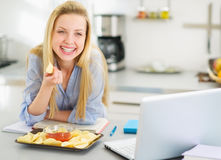 Muchacha que come microprocesadores mientras que estudia en cocina moderna Fotografía de archivo