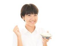 Muchacha que come un arroz Imagenes de archivo