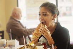 Muchacha que come un bocadillo grande Fotografía de archivo libre de regalías